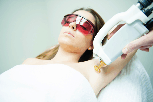 An aesthetic technician uses laser technology to treat hair growth on a client's underarms.