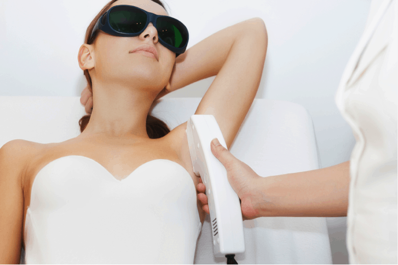 A young woman has unwanted underarm hair removed with the help of laser treatment