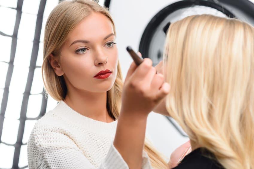 A makeup artist applies setting powder to her client's face