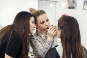 makeup teacher training her student girl to become makeup artist. Makeup lesson at beauty school. Make-up artist work in her studio. Real people. Closeup of visagiste applying makeup