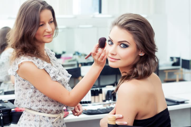 Make-up artist applying powder with a brush on model's cheeks, selective focus on model looking at camera