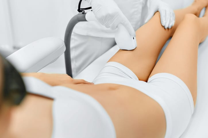 Body Care. Legs Laser Hair Removal. Beautician Removing Hair Of Young Woman's Leg. Laser Epilation Treatment In Cosmetic Beauty Clinic. Hairless Smooth And Soft Skin. Health And Beauty Concept.