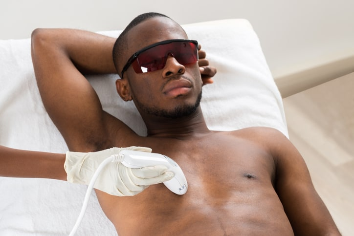 Therapist Giving Laser Epilation On Young African Man's Chest