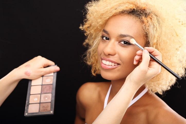 Make-up artist doing natural make up for mulatto.
