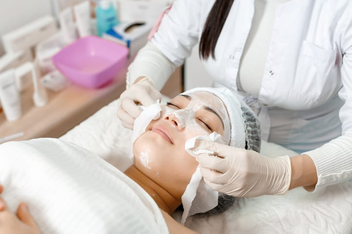 The beautician wipes the mask off the face of the young patient woman