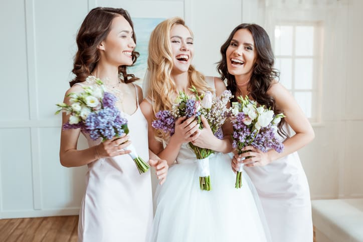 beautiful laughing bride with bridesmaids holding bouquets