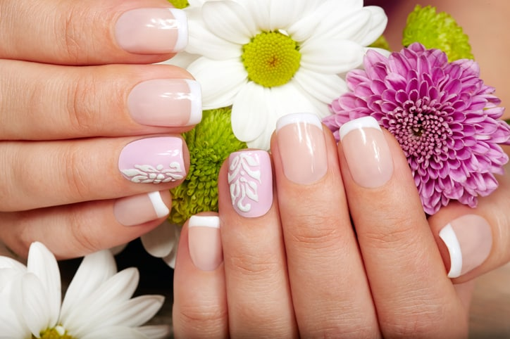 Hands with french manicured nails and a bouquet of flowers
