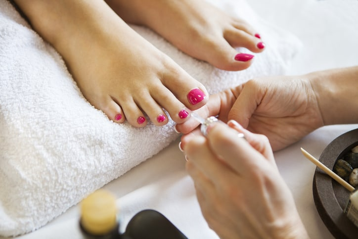Woman in nail salon receiving pedicure by beautician. Close up of female feet resting on white towel