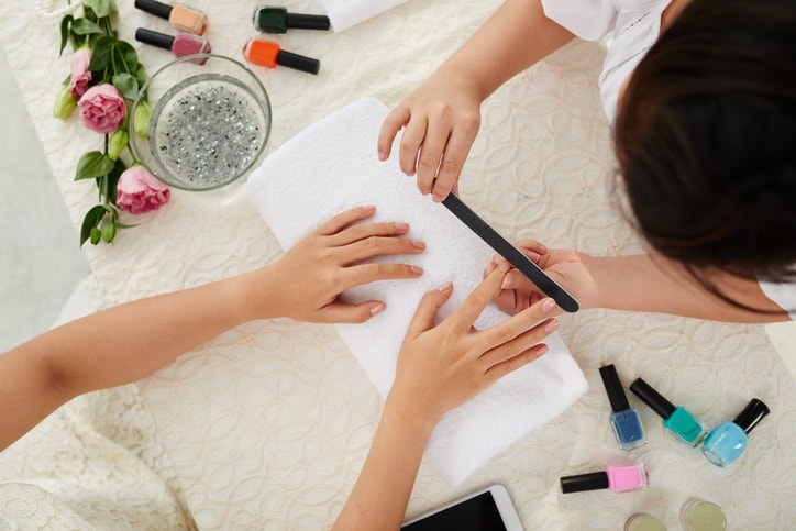 Manicurist filing nails of female client, view from above