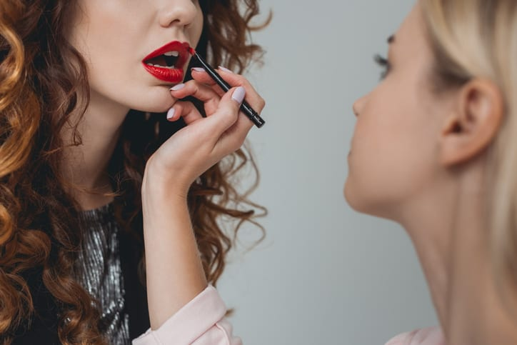 cropped view of attractive model and makeup artist applying lipstick in photo studio