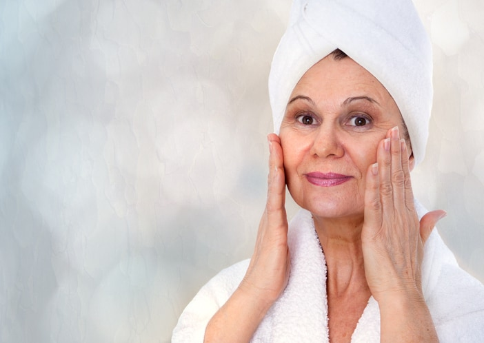 Spa concept portrait. Aged good looking woman with white towel on her head