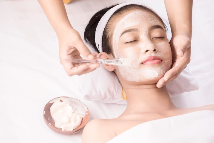 Young girl with facial mask at beauty salon