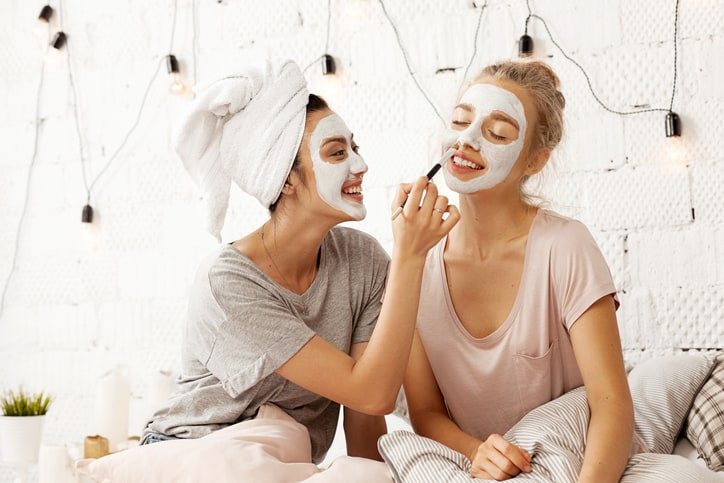Portrait of happy smiling young women sitting in light bedroom and making fun using brush for applying facial cleansing mask. Home beauty treatments concept