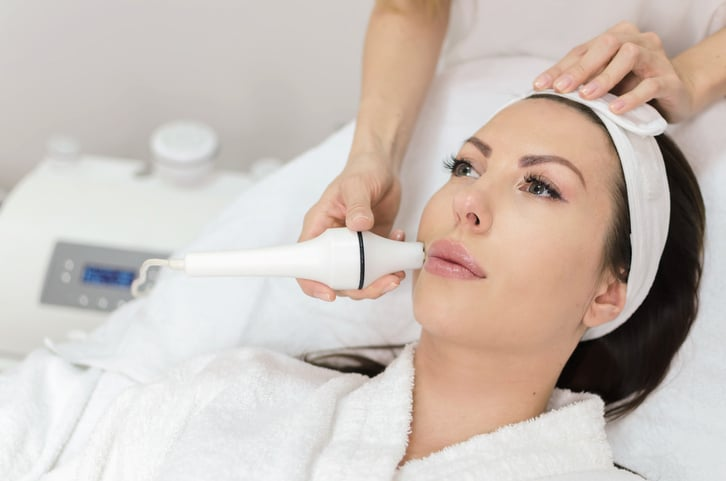 Adult woman enjoying in face massage after hyaluron injection in lips in wellness center. Portrait of beautiful female in ordination.