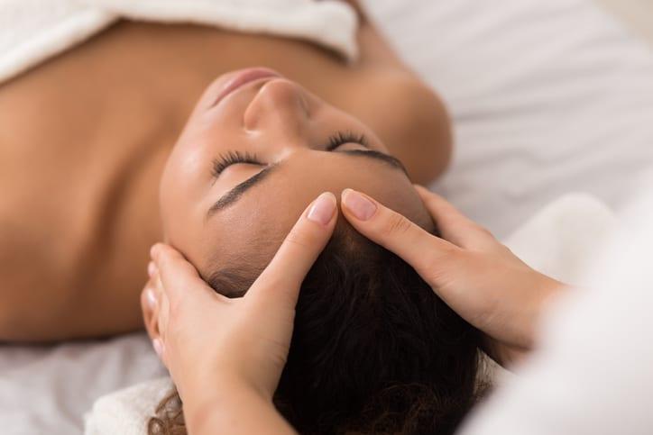African-american woman enjoying anti aging facial massage in spa salon
