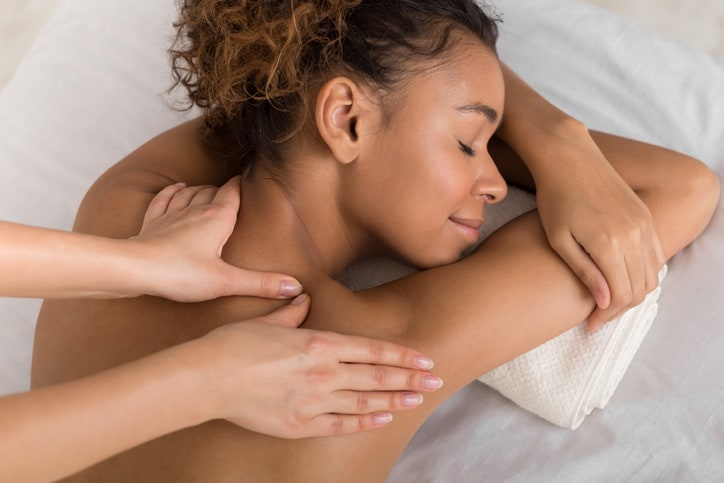 African-american woman enjoying shoulder massage, lying with closed eyes in spa center