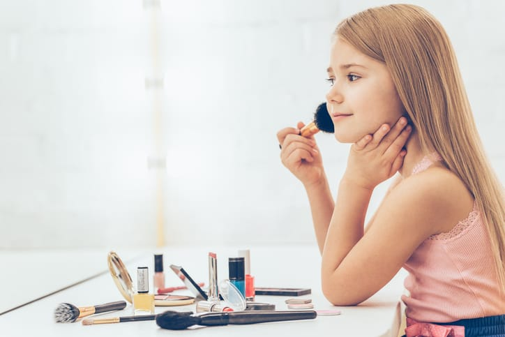 Side view of cheerful little girl applying make-up and looking at her reflection in mirror while sitting at the dressing table