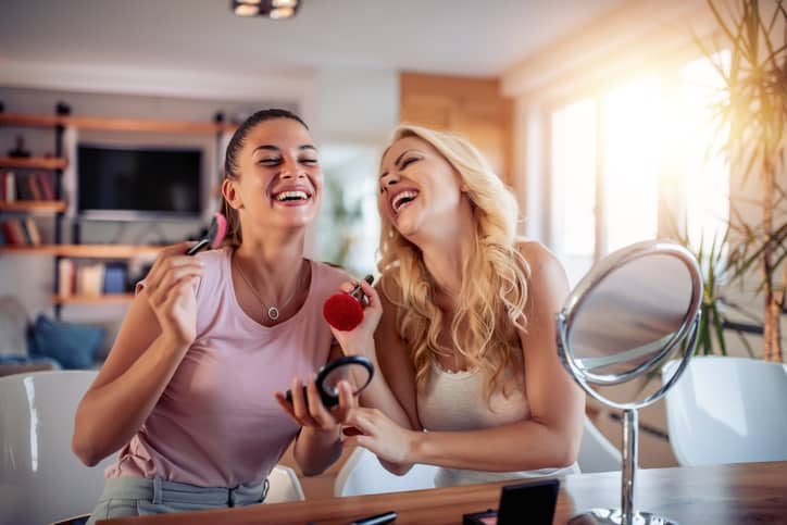 Two happy girls applying make up at home, having fun together.