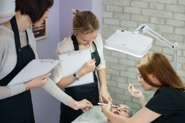 Professional cosmetology courses. Permanent makeup. Female beautician sketching up symmetrical eyebrows.
