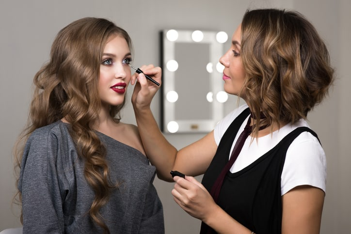 Makeup process, makeup artist colors model at salon. Portrait of two beautiful women