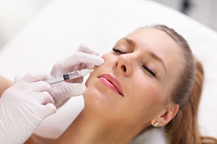 Hands of cosmetologist making botox injection in female lips