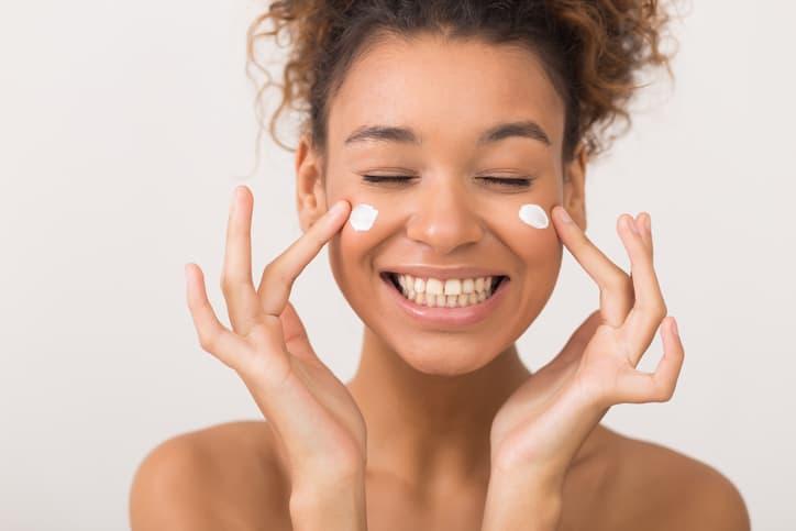 Skin care. Laughing girl applying moisturizing cream on her face over white background