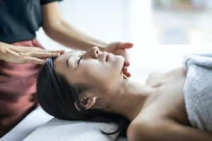 woman performing a facial on a client